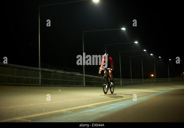 Cyclist cycling on track at velodrome, outdoors - Stock Image