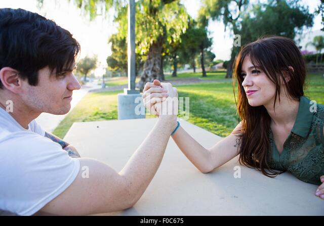 Young couple arm wrestling at picnic bench in park - Stock Image