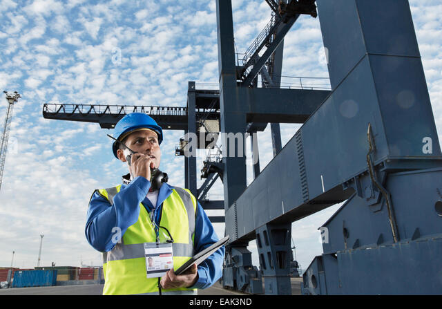 Worker using walkie-talkie under cargo crane - Stock Image