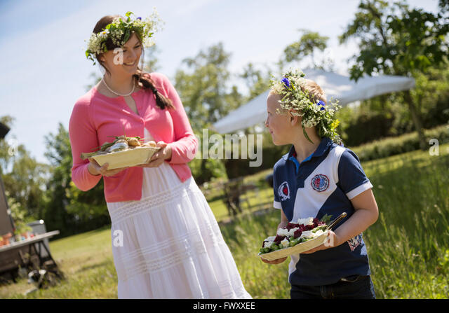 Sweden, Skane, Girl (6-7) talking with mother during festival - Stock Image