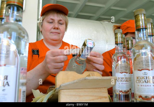 Pasting excise stamps and company labels on vodka bottles on a Yuzhnaya Stolitsa distillery conveyor line - Stock Image