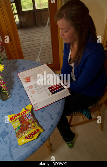 American female teenager studying for high-school test in chemistry. - Stock Image