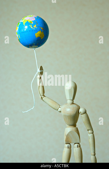 Wooden artist's manikin holds globe on a string - Stock Image