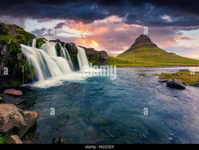 Summer sunset on famous Kirkjufellsfoss Waterfall and Kirkjufell mountain. Dramatic evening scene on Snaefellsnes - Stock Image