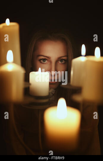 Dark candlelight portrait of a young woman . Gothic and surreal concept - Stock-Bilder