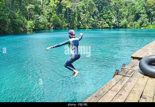 A girl jumping into Labuan Cermin Lake - Stock Image