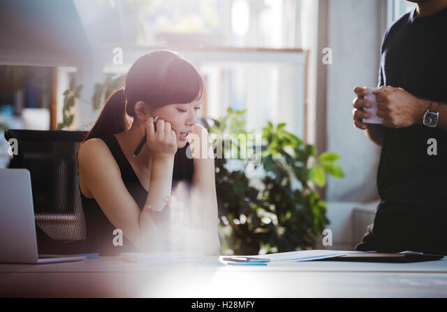 Shot of young woman sitting at her desk and talking with male colleague standing by. Coworkers working together - Stock Image