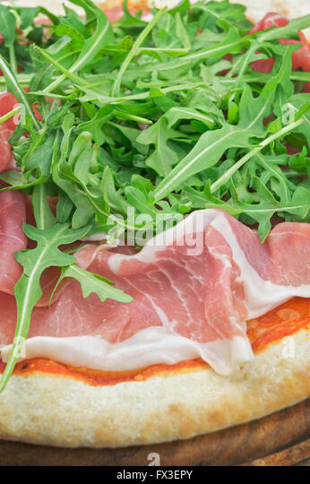 Pizza with salad rocket and ham on wooden plate - Stock Image