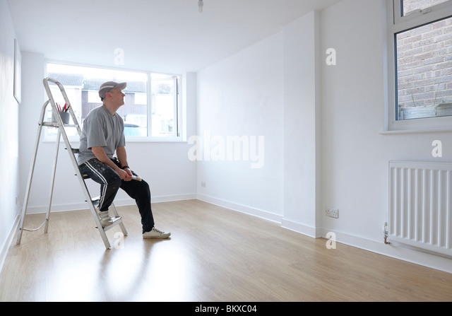 man sitting on ladder looking at newly decorated white painted room - Stock Image