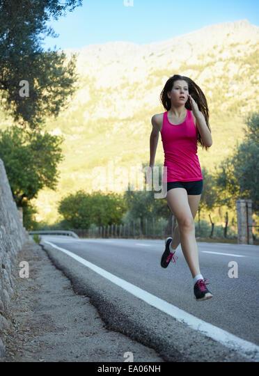 Teenage girl running on road, Majorca, Spain - Stock Image