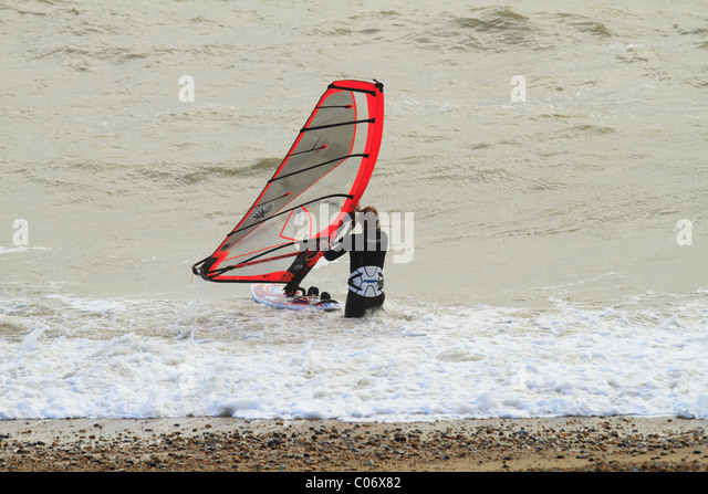 A wind surfer enters the water at Eastbourne, East Sussex, England. - Stock Image