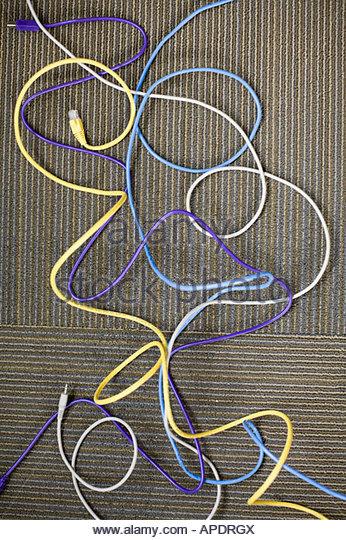 Assorted computer wires on floor - Stock Image