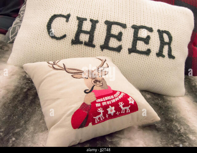 A reindeer pillow and cheer pillow on a gray bed pillow. - Stock Image