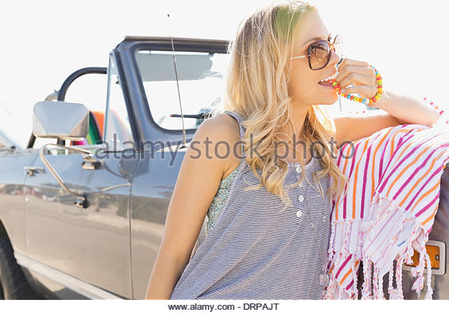 Woman leaning against off-road vehicle eating candy - Stock Image