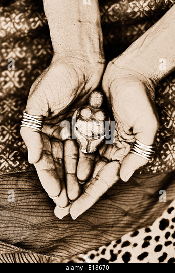 A woman's hands holding a Gaia figurine. - Stock Image