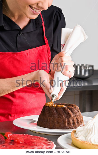 Female chef icing a cake - Stock Image