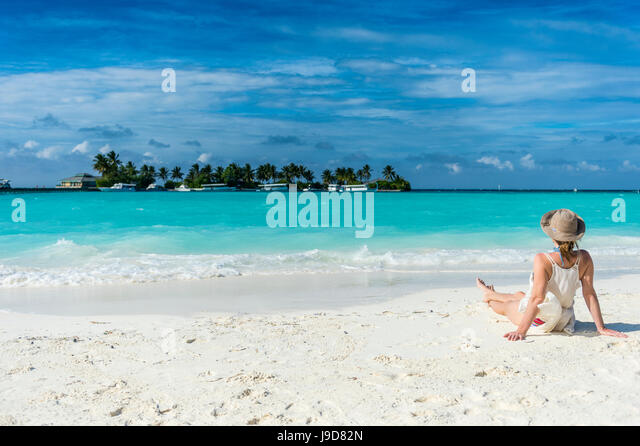 Woman sitting on a white sand beach enjoying the turquoise water, Sun Island Resort, Nalaguraidhoo island, Ari atoll, - Stock Image
