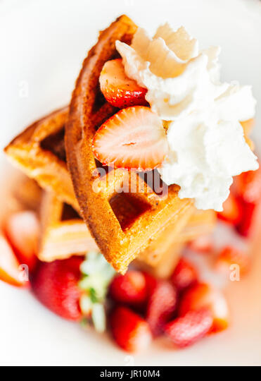 waffles with sweet whipped cream topping and strawberries - Stock Image