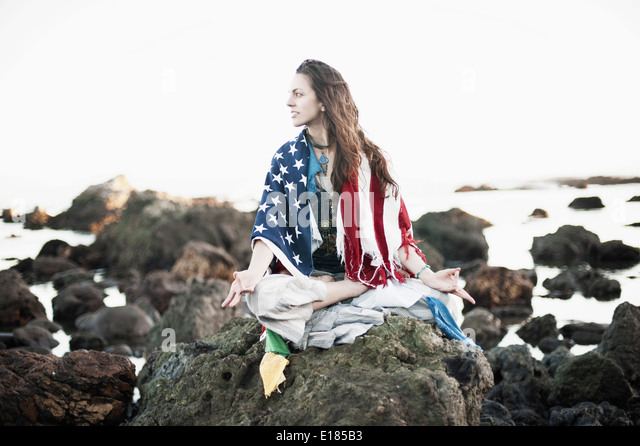 Beautiful woman draped in the american flag and tibetan prayer flags. - Stock Image