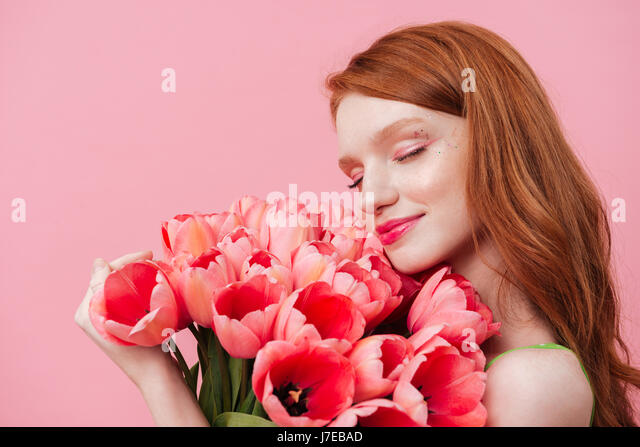 Young pretty woman touching and sniffing with closed eyes pink flowers - Stock Image