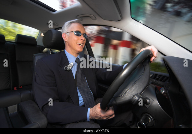 business work job career old elderly man sitting driving steering fast happy in new car holding wheel sunroof sunglasses - Stock Image