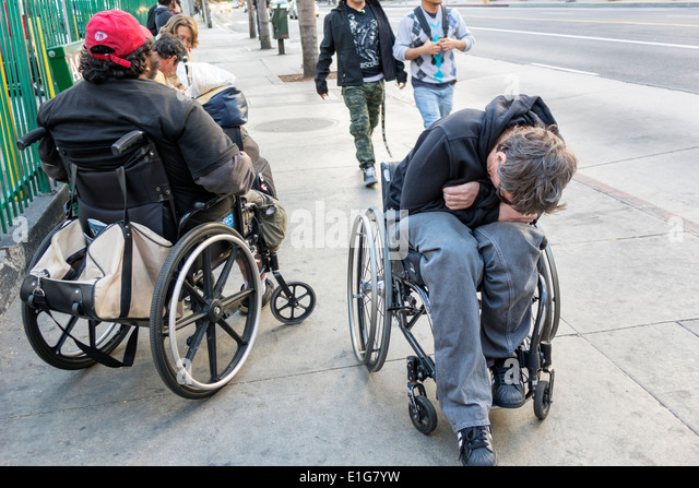 Los Angeles California CA L.A. Downtown sidewalk man men disabled wheelchair amputee bus stop - Stock Image