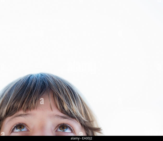 Cropped close up portrait of girl looking upward - Stock Image