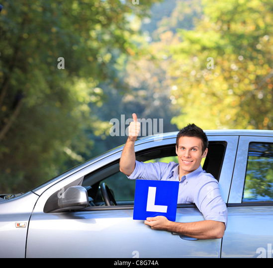 Happy male in his car holding a L sign and giving thumb up - Stock Image