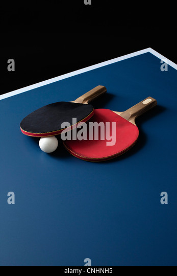 Table tennis bats and a ball on a table - Stock Image