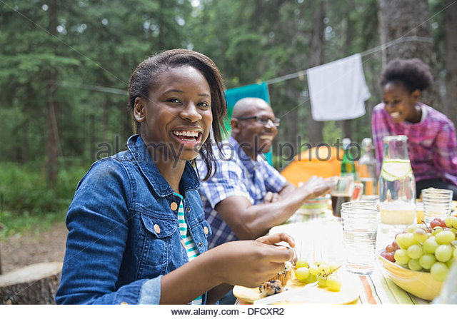 Portrait of happy girl having meal with family at campsite - Stock Image