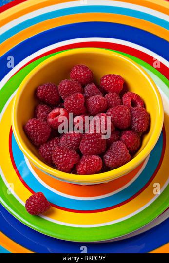 Raspberries in yellow bowl on plate - Stock-Bilder