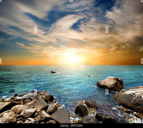 Beach at sunset, clear sea and blue cloudy sky - Stock Image