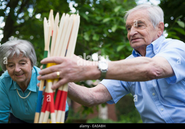 Grandfather and grandmother with giant pick up sticks - Stock Image