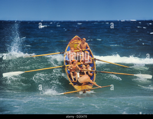 Sydney, lifesavers surfboat passing a breaker during a competition at the North Narrabeen Beach surf carnival - Stock Image