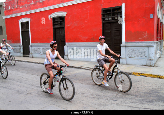 Peru Lima Barranco District neighborhood Calle Melgar street scene building red wall bicycle riding pedaling cycling - Stock Image