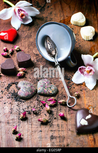 Chocolate candies heart shaped with dry tea roses and tea cup for Valentine's Day. - Stock Image
