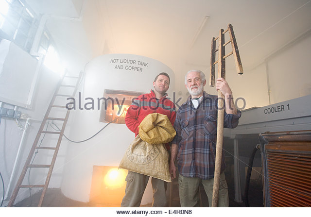 Two brewers pose for a photograph by the Hot Liquor Tank at the original brewhouse at Traquair House Brewery, Traquair - Stock-Bilder
