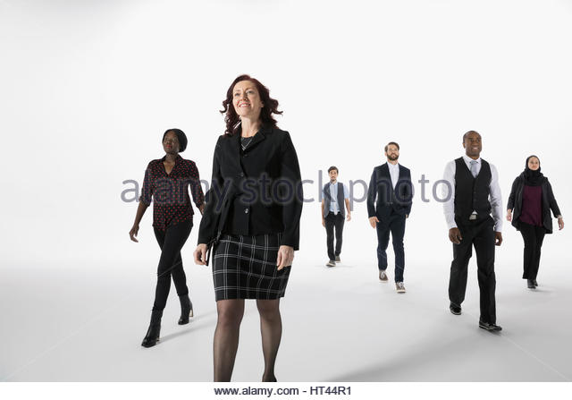 Confident businesswoman leading business people against white background - Stock-Bilder