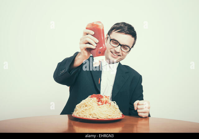 Happy consumerism concept. Happy businessman pouring ketchup on huge dish of pasta. - Stock Image