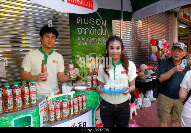 Thailand Bangkok Samphanthawong Chinatown Yaowarat Road Asian man woman free sample tea bottled new product promotion - Stock Image