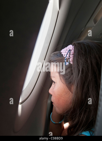 child on an airplane,looking through the window - Stock Image