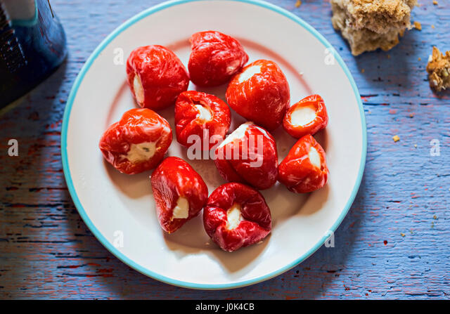 Peppers stuffed with feta cheese on white plate - Stock Image