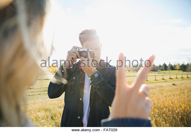 Young man photographing girlfriend gesturing peace sign - Stock-Bilder