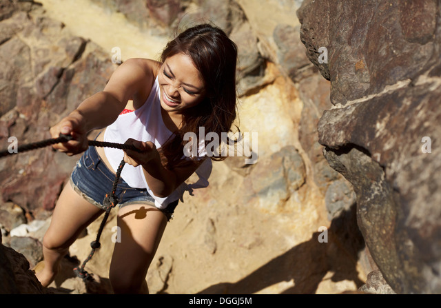 Young woman climbing rocks, Palos Verdes, California, USA - Stock Image