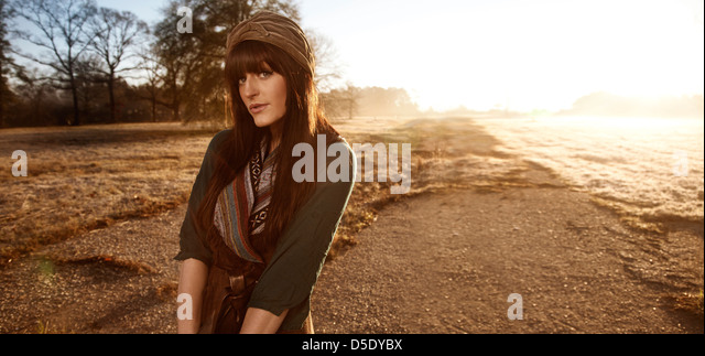 Woman standing in field with sunlight over shoulder - Stock Image