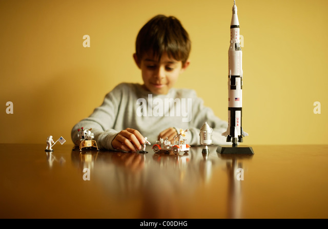 Boy with model Saturn V Apollo moon rocket, astronauts, lunar module and lunar rover. - Stock Image