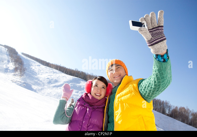 Happy young couple taking pictures in ski resort - Stock Image