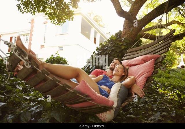 Portrait of an affectionate young couple lying on a hammock looking away smiling. Romantic young man and woman on - Stock-Bilder