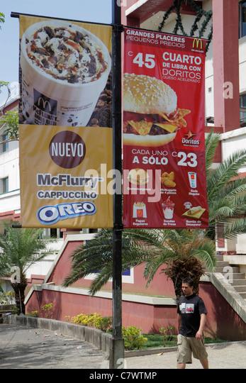Managua Nicaragua Avenida Simon Bolivar Plaza Inter street scene Hispanic man walking sign banner advertising marketing - Stock Image