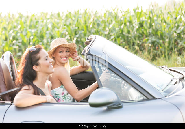 Happy friends enjoying road trip in convertible - Stock Image